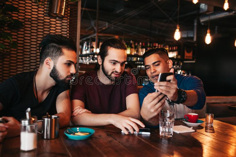 Group of mixed race young men talking and using phone in lounge bar. Multiracial friends having fun in cafe royalty free stock photo