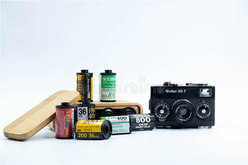 A Group of 35mm Negative films : Fujifilm ,Kodak , Agfa ,Lomography and Rollei 35T German Camera and The Wooden Film Case. Isolate on White Background stock images