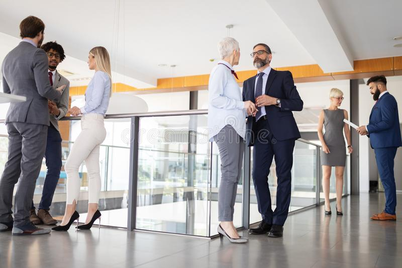 Group of modern business people chatting during coffee break standing in office building stock photo