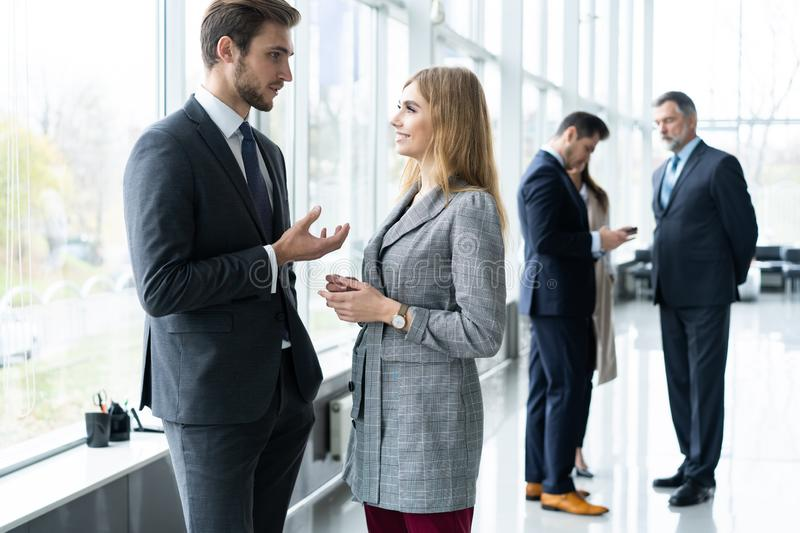 Group of modern business people chatting during coffee break standing in sunlit glass hall of office building. stock images