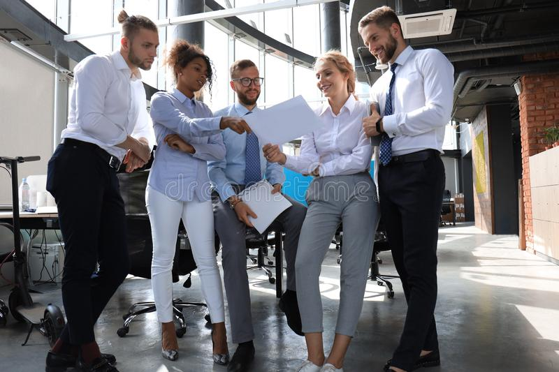 Group of modern business people are talking and smiling while standing in the office royalty free stock images