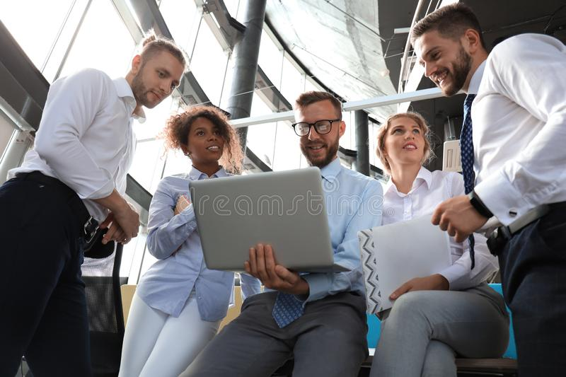 Group of modern business people working together in creative office while standing near the desk royalty free stock photo