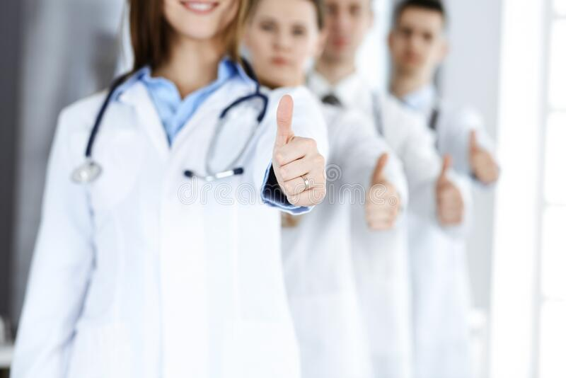 Group Of Modern Doctors Standing As A Team With Thumbs Up ...