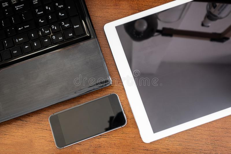 Group of modern electronic devices, computer laptop, digital tablet and mobile smart phone on wooden table stock images