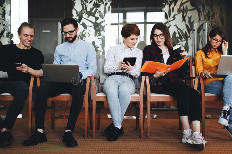 Group of modern hipster friends working together for contemporary gadgets in open space office. Friendship creative stock photos