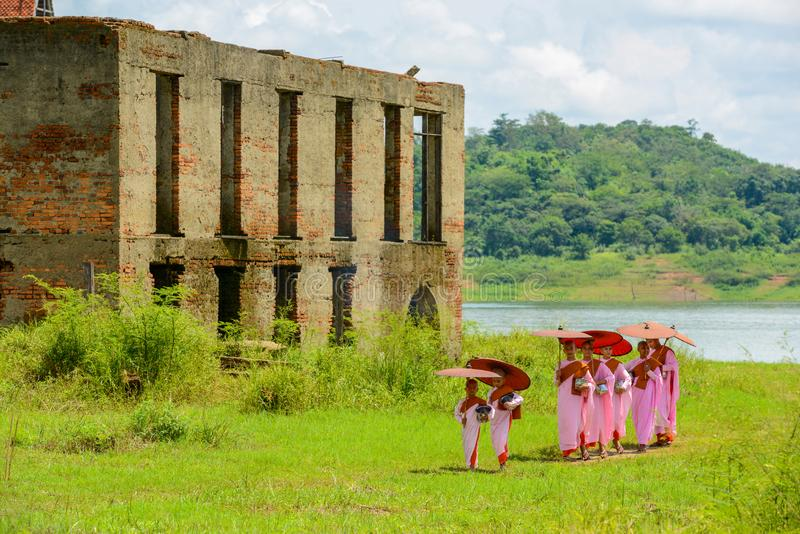 Group of Mon nuns walking out of ruined Buddhist church. Kanchanaburi, Thailand - July 24, 2016: Group of Mon nuns in pink robes holding umbrella walking out of royalty free stock photos