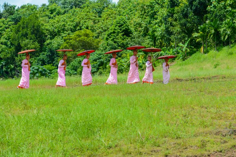 Group of Mon nuns walking toward to ruined Buddhist church. Kanchanaburi, Thailand - July 24, 2016: Group of Mon nuns in pink robes holding umbrella walking royalty free stock photography
