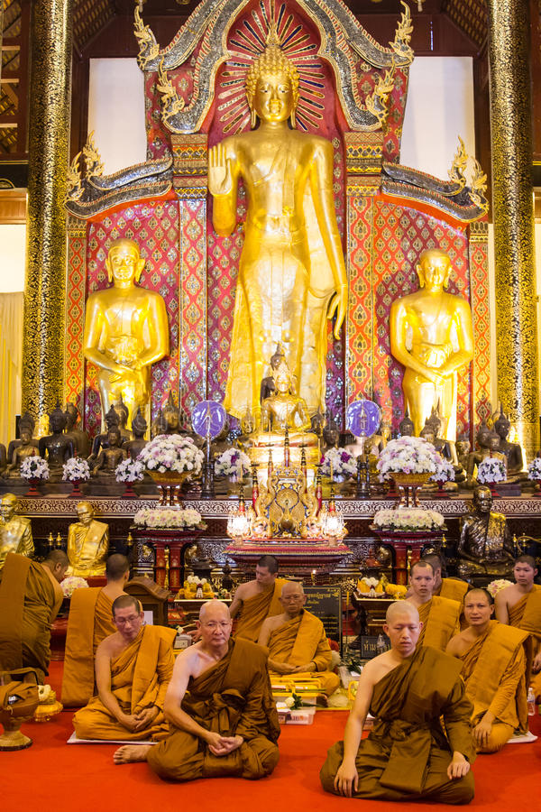 Group of monks in sitting in front of Buddha standing images ins. CHIANG MAI, THAILAND - NOVEMBER 7, 2015: Group of monks sitting in front of Buddha images royalty free stock photos