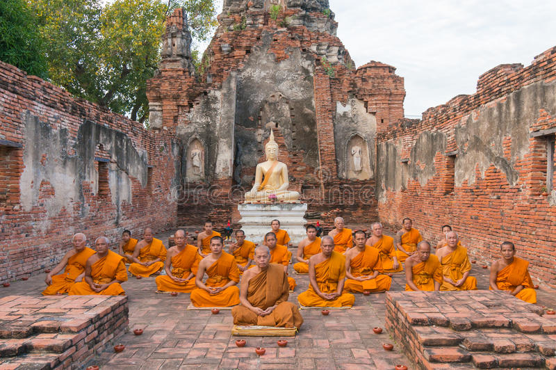 Group of monks sitting in ruined building of Wat Choeng Tha Temple royalty free stock photos