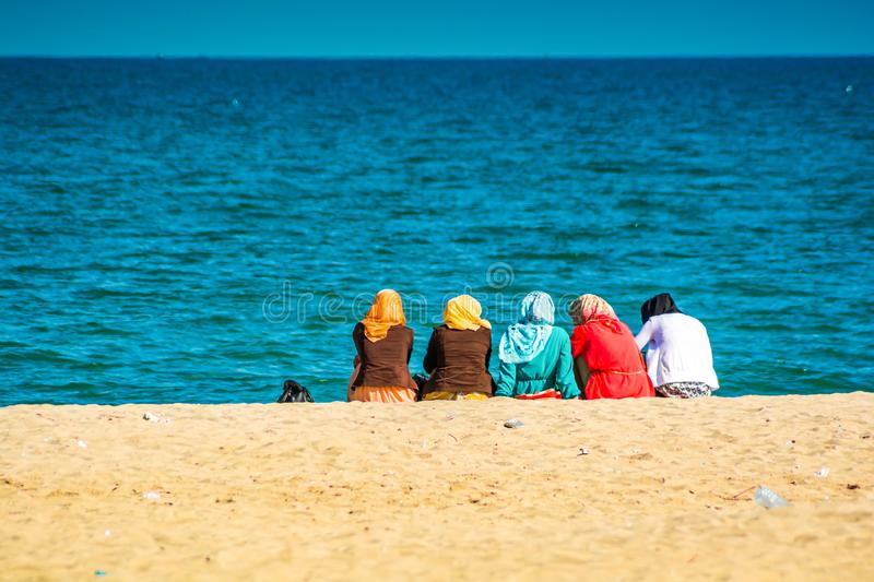 Group of Moroccan women sitting on the beach royalty free stock photos