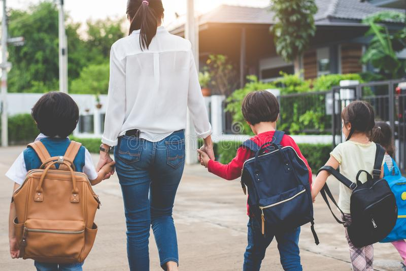 Group of mother and kids holding hands going to school with schoolbag. Mom bring children walk to school by bus together with sat. Chel. Back to school and stock image