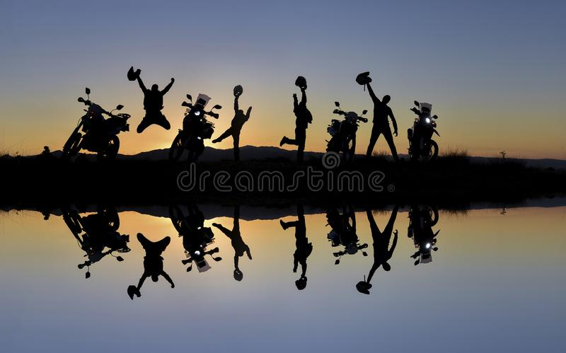 Group of motorcyclists celebrating. A group of motorcyclists celebrating after a road trip with sun on their back and reflection stock photos