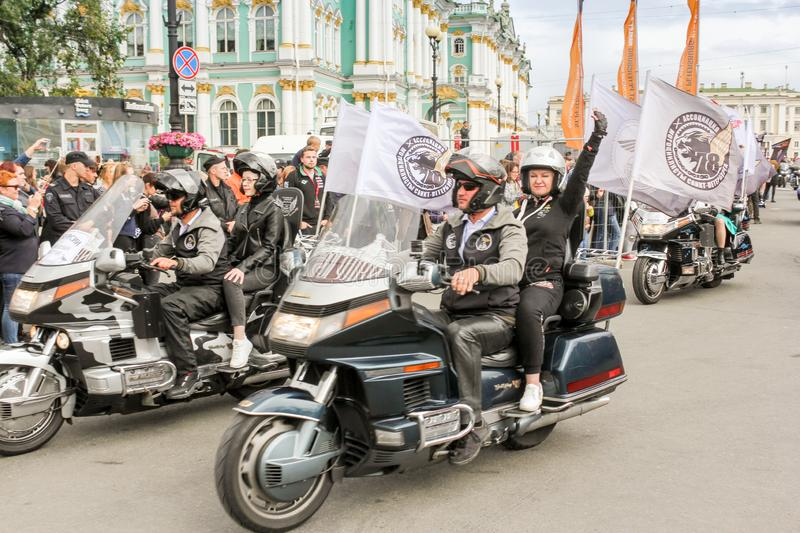 A group of motorcyclists with flags drives by royalty free stock images