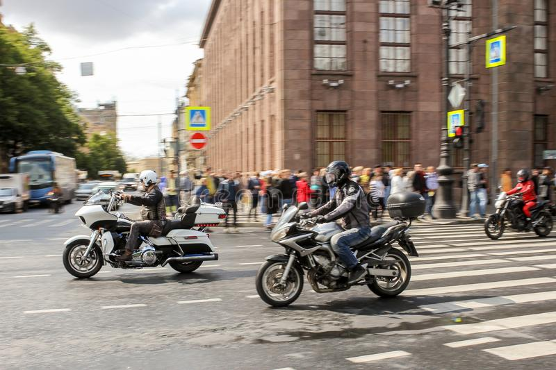 A group of motorcyclists pass by spectators stock photos