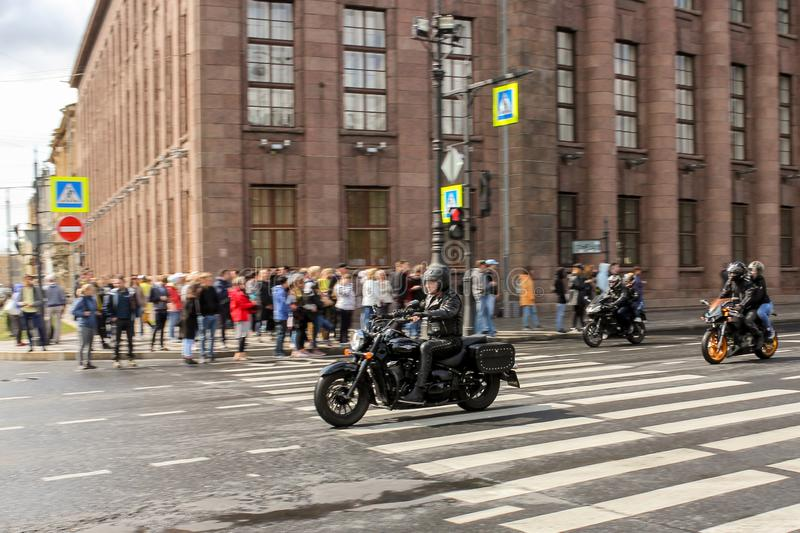 A group of motorcyclists pass by spectators stock photo