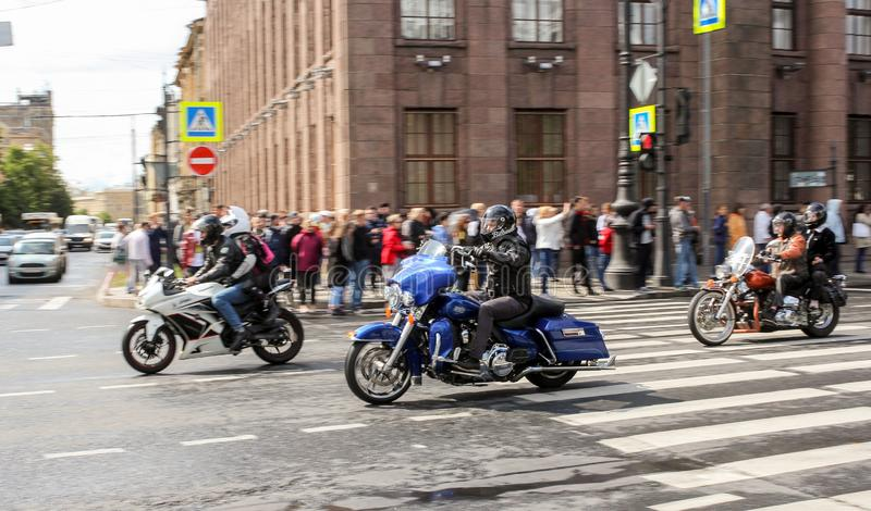 A group of motorcyclists pass by spectators royalty free stock photography