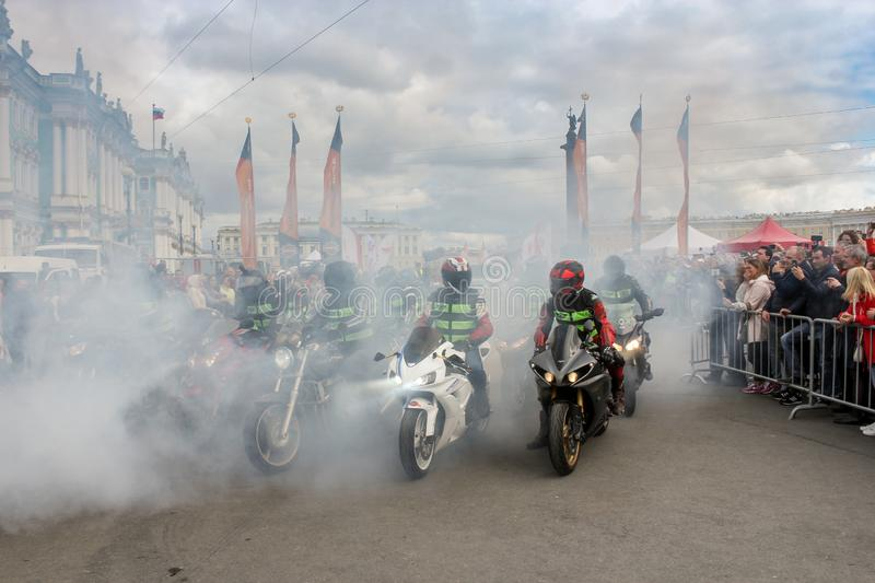 A group of motorcyclists in smoke from rubber stock photography