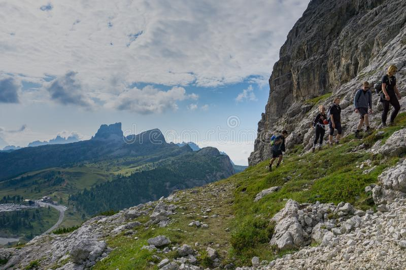 Group of mountain climbers hiking up a mountain side to a hard climbing route. In the Dolomites of Italy royalty free stock image