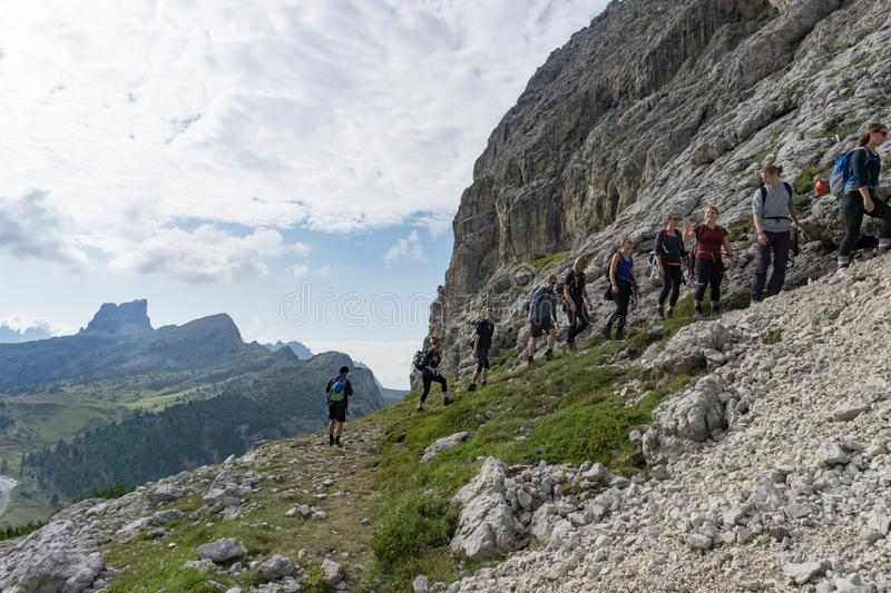 Group of mountain climbers hiking up a mountain side to a hard climbing route stock image
