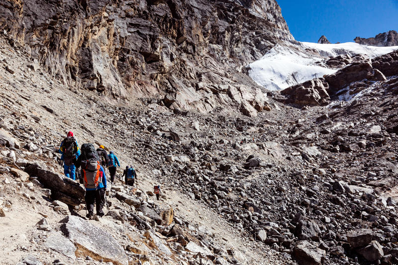 Group of Mountain Climbers walking on rocky slope toward Pass stock image