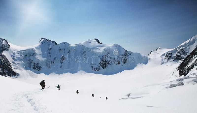 A group of mountaineers climbs to the top of a snow-capped mountain. Climbers are hiking on mountain peaks ridge. Beautiful mountaineering tourism trekking royalty free stock images