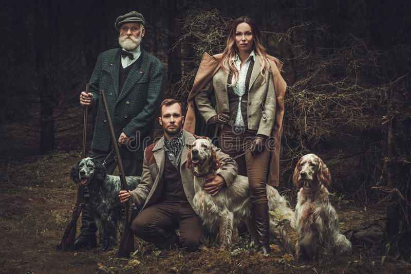 Group of multi-age hunters with dogs and shotguns in a traditional shooting clothing, posing on a dark forest background stock photo
