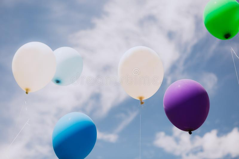 Group multi colored balloons ribbons outside sky. Group of multi colored balloons with ribbons outside against the sky and clouds, holiday, colorful, cheerful royalty free stock images