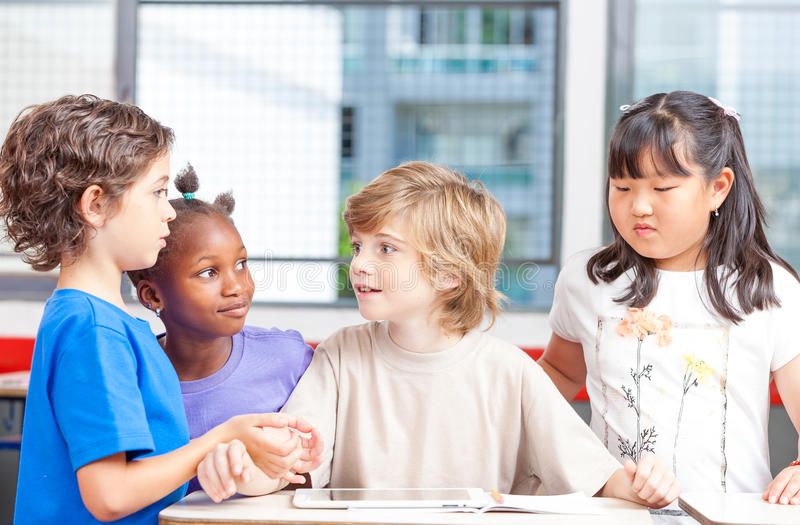 Group of multi ethnic elementary students working with tablet at royalty free stock image