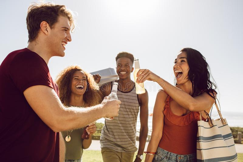 Friends going on a picnic. Group of multi-ethnic friends having beers while walking to the picnic spot. Men and women friends going on a picnic on a summer day royalty free stock photos