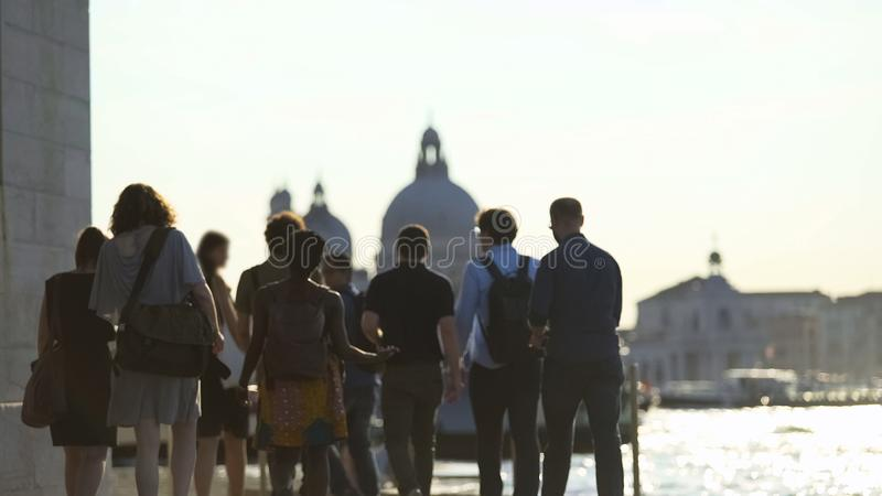 Group of multi-ethnic tourists walking in Venice, view of Grand Canal, tourism stock photos