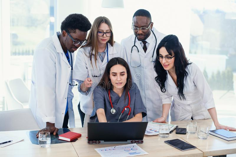 Group of multi national doctors using laptop for discussing analysis in the conference room. Side view. stock photography