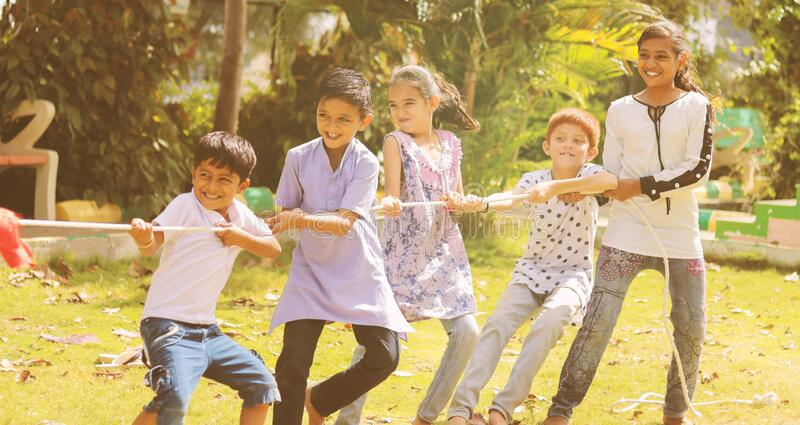 Group of multi racial children playing Tug of war game kindergarten - Multi ethnic kids playing outdoor games againt royalty free stock image