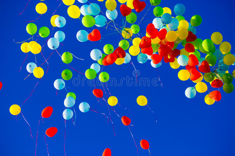 Group of multicolored helium filled balloons in the sky. Group of multicolored helium filled balloons in the blue sky royalty free stock image