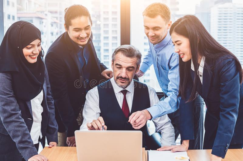 Group of multiethnic business people trainning by executive senior boss in modern office with laptop computer. Startup team stock photo