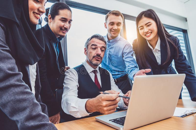 Group of multiethnic business people trainning by executive senior boss in modern office with laptop computer. Startup team royalty free stock photo