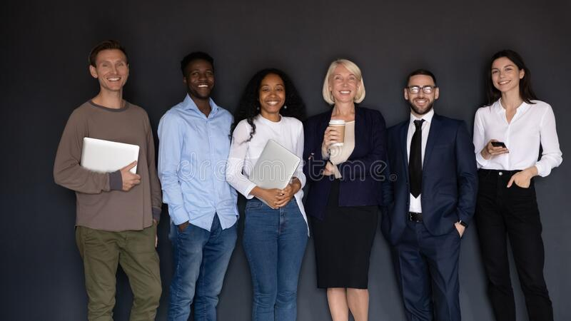 Group of multiethnic corporate staff holding gadgets smiling posing indoors stock image