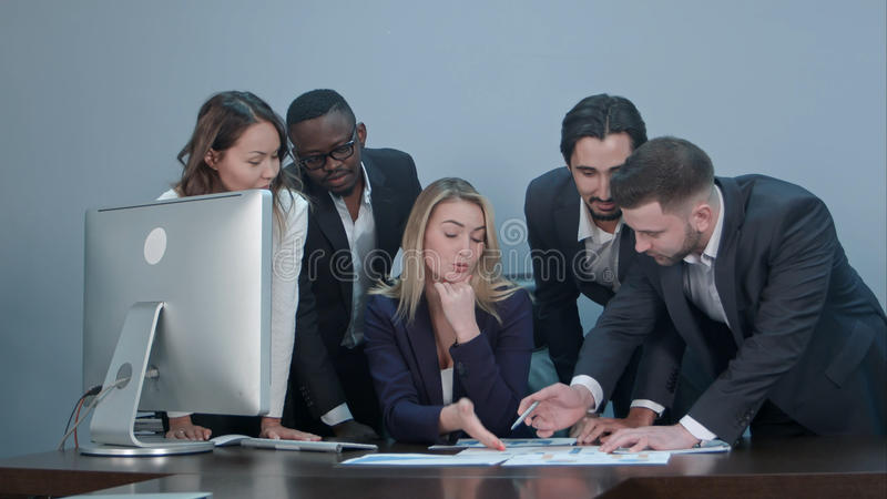 Group of multiethnic diverse young business people in a meeting standing around a table with serious expressions royalty free stock photography