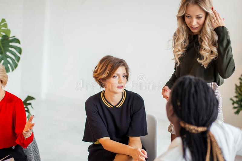 Group of Multiethnic Female team working in Office. Serious caucasian female with her partners check notification on smart phone, work on report at laptop royalty free stock photography