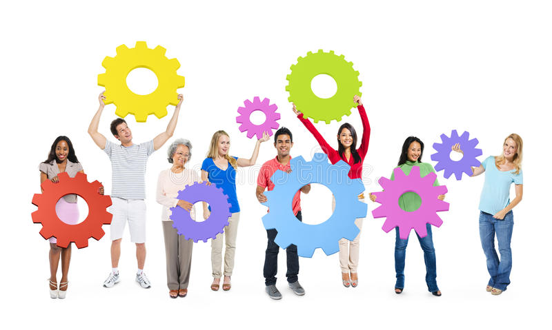 Group of Multiethnic People Holding Colorful Cogs.  stock photo