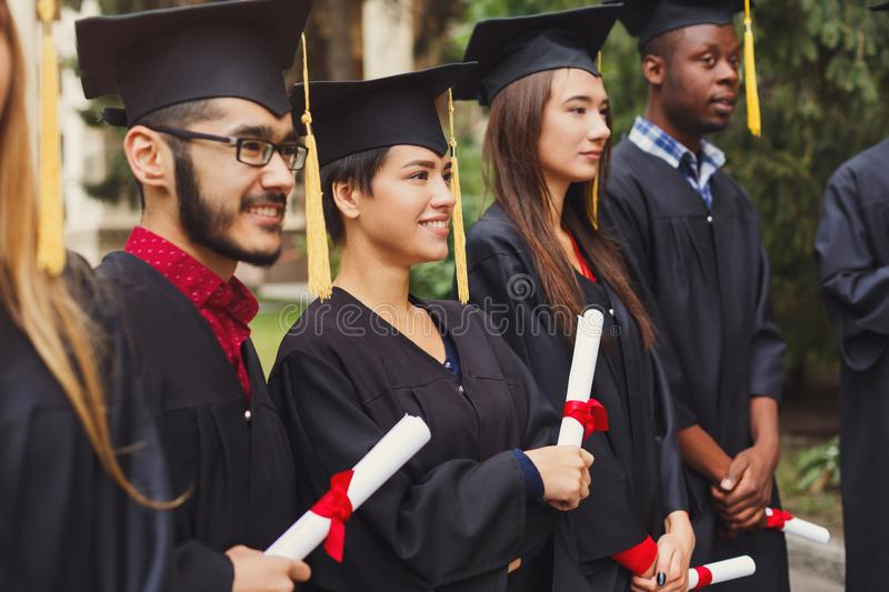 Group of multiethnic students on graduation day. Group of multiethnic students holding their diplomas on graduation day, Happy people celebrating education stock image