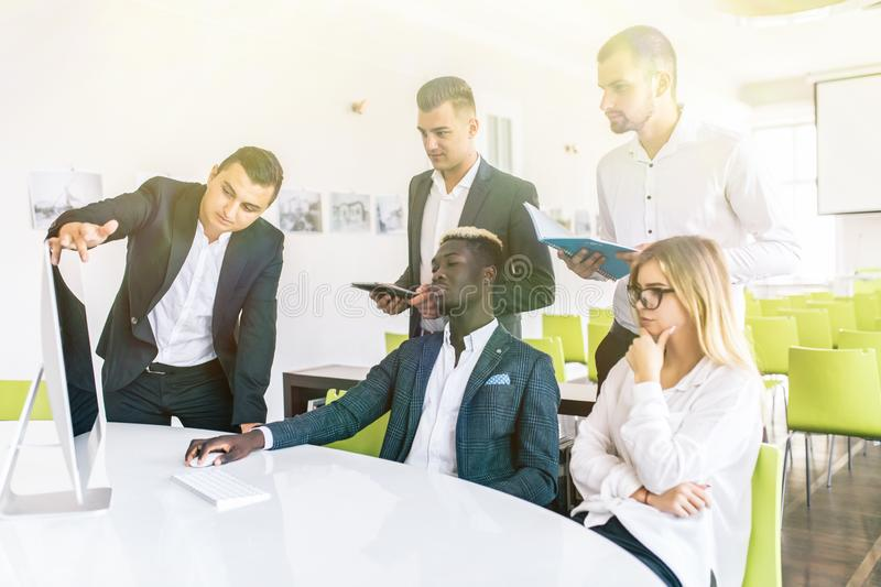 Group of multinational entrepreneurs working using a laptop and holding a document royalty free stock photo