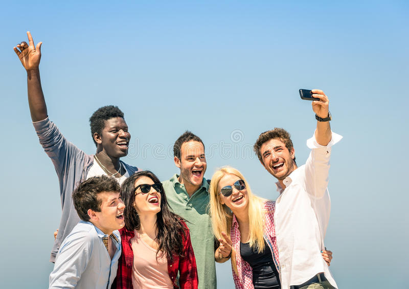 Group of multiracial friends taking a selfie on a blue sky. Group of multiracial friends taking a selfie on the blue sky - Concept of happiness and friendship