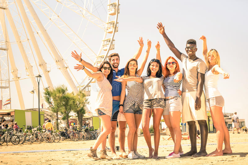 Group of multiracial happy friends cheering at ferris wheel. International concept of happiness and multi ethnic friendship all together against racism for royalty free stock images