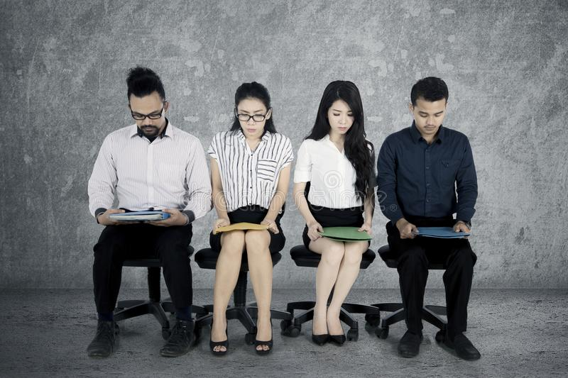 Strained workers waiting for a job interview. Group of multiracial workers sitting on the office chair and looks strained while waiting for a job interview royalty free stock photos