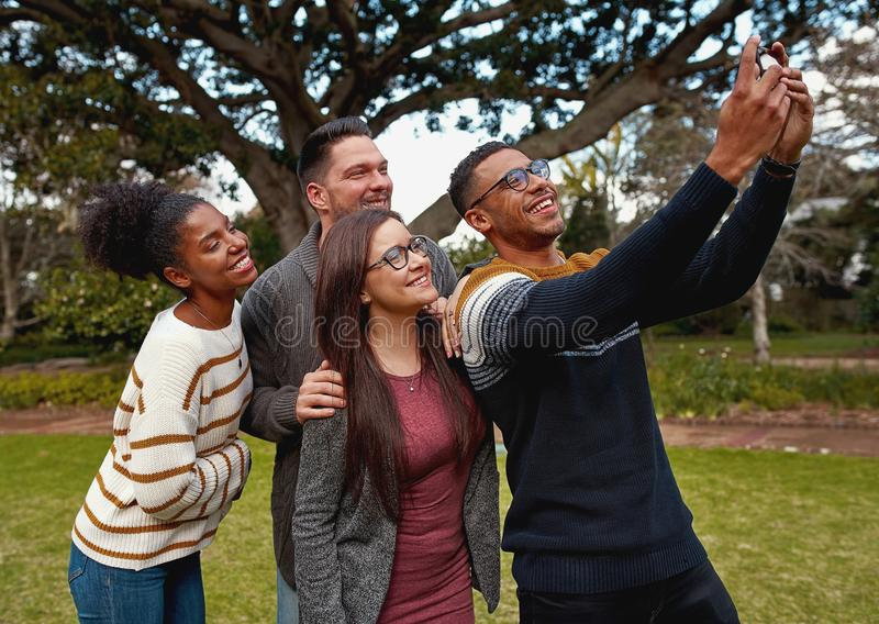 Group of multiracial young friends standing together in a green park taking a selfie on mobile phone smiling - a summer royalty free stock photography