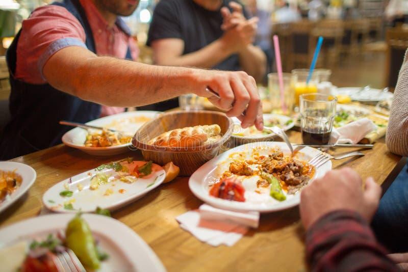Arab men in restaurant enjoying Middle Eastern food. Group of Muslim people in restaurant enjoying Middle Eastern food. Selective focus stock photography