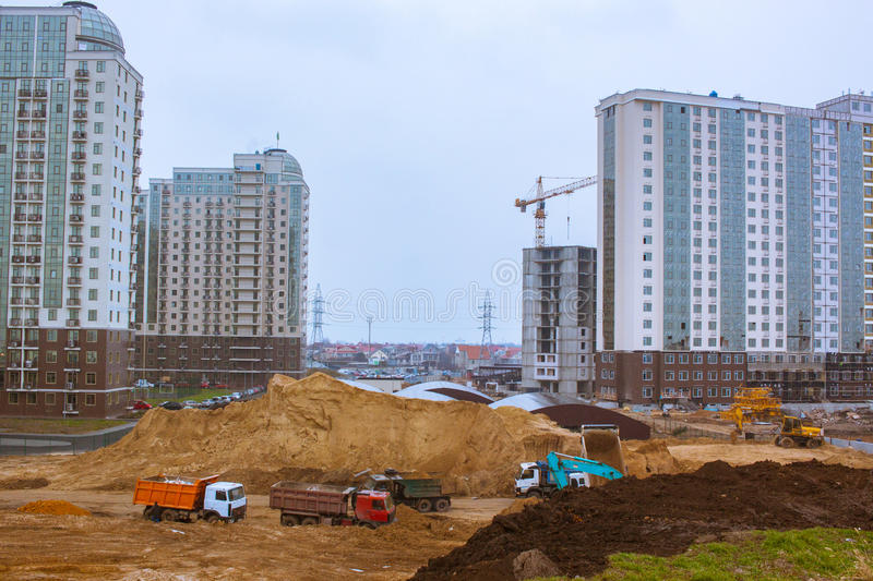 Group of new buildings and construction yard with cargo cars. Process of building,tower cranes brick and concrete buildings royalty free stock photos