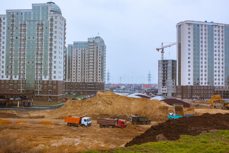 Group of new buildings and construction yard with cars. Process of building,tower cranes brick and concrete buildings royalty free stock photos