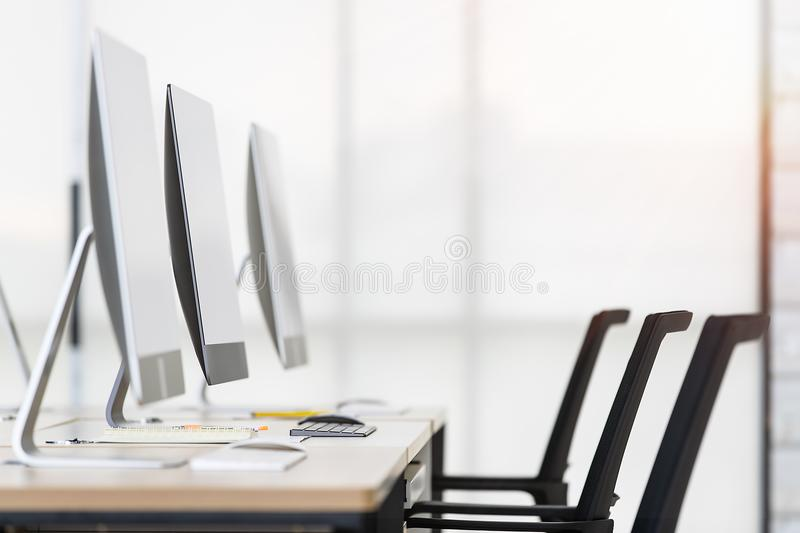 Group of new clean computers on desk in modern office with windows in background. Group of new computers on desk in modern office with windows in background royalty free stock photo