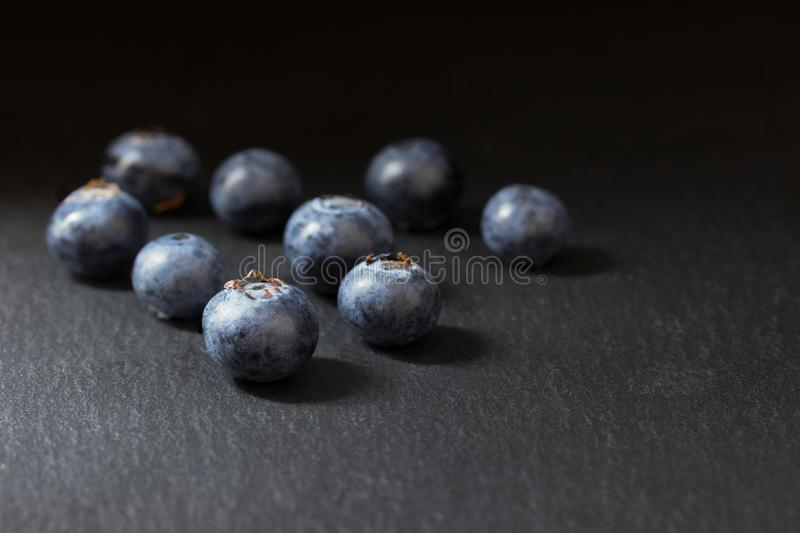Nine fresh blueberries on a dark stone table royalty free stock photos